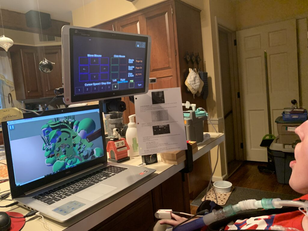 Jack's gaming setup as he plays the Painted Waters prototype. One monitor display his Eyegaze controls and the other monitor displays the game.